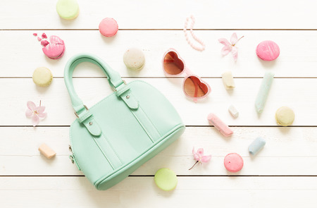 Pastel theme mood board with fashion accessories (bag, sunglasses) for girls. White rustic wooden background. Flat lay composition (from above, top view).