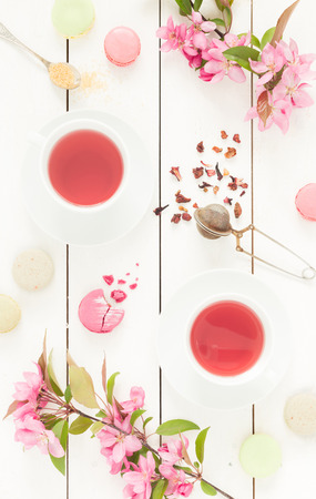Photo for Pink fruity tea and pastel french macarons cakes on rustic white wooden background. Dessert in a garden. Flat lay composition (from above, top view). - Royalty Free Image