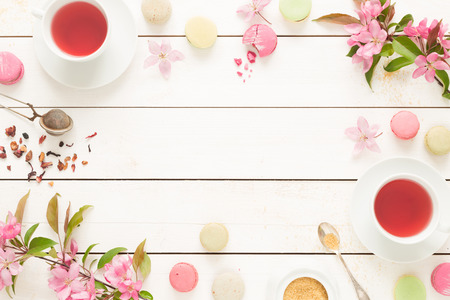 Pink fruity tea and pastel french macarons cakes on rustic white wooden background. Dessert in a garden. Flat lay composition (from above, top view). Free text space.