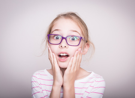Surprised or shocked face of eight years old pretty blond caucasian child girl in violet glasses. Shock - facial expression. Layout with free copy space.
