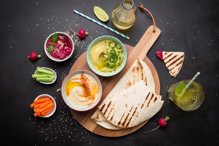 Photo pour Colorful vegetarian snacks (appetizers) table. Various dips with pita bread. Black chalkboard as background. Flat lay composition from above (top view). Healthy diet or lifestyle concept. - image libre de droit