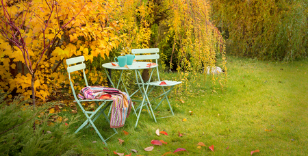 Photo pour Colorful autumn garden nook - pastel green table, cups of hot tea, chairs and blanket. Outdoor fall relaxation scenery - countryside lifestyle concept. - image libre de droit