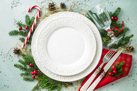 Photo pour Elegant christmas table setting design captured from above (top view, flat lay). Empty white plate, glass, cutlery, candy cane and decorations. Background layout with free text (copy) space. - image libre de droit