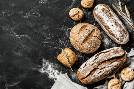 Photo pour Bakery - gold rustic crusty loaves of bread and buns on black chalkboard background. Still life captured from above (top view, flat lay). Layout with free copy (text) space. - image libre de droit