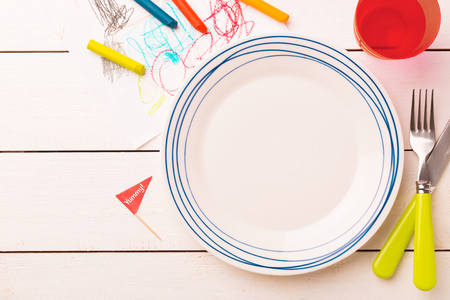 Photo pour Table setting for kids. Empty plate on white planked wooden table with colorful decorations around - captured from above (top view, flat lay). Layout with free text (copy) space. - image libre de droit