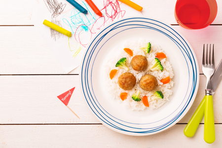 Photo pour Small kid's meal - meatballs, rice, broccoli and carrot. Colorful dinner on white wooden table. Plate captured from above (top view, flat lay). Layout with free copy (text) space. - image libre de droit