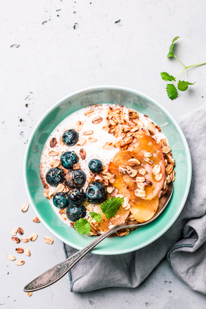 Photo pour Healthy breakfast or dessert. Yoghurt with oat flakes, blueberries, apples and honey in pastel blue bowl on grey stone background. Captured from above (top view, flat lay). Free copy (text) space. - image libre de droit