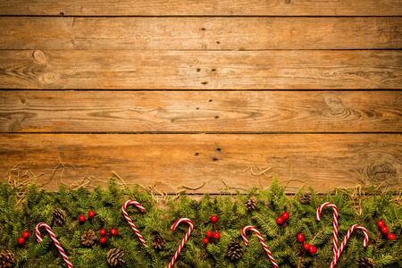 Photo pour Wooden christmas background with decorative green and red ornament (natural pine branches, candy canes). Layout with free copy (text) space. Captured from above (top view, flat lay). - image libre de droit