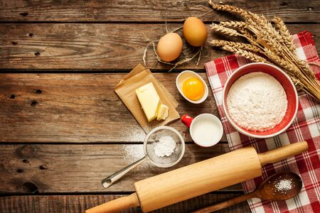 Photo for Baking cake in rural kitchen - dough recipe ingredients (eggs, flour, milk, butter, sugar) on vintage wooden table from above. Background layout with free text space. - Royalty Free Image