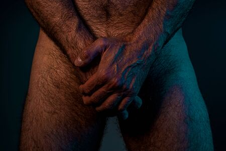 Foto de Naked man holding hands on his crotch. Male intimate body part close up - health care concept. Dark moody night light. - Imagen libre de derechos