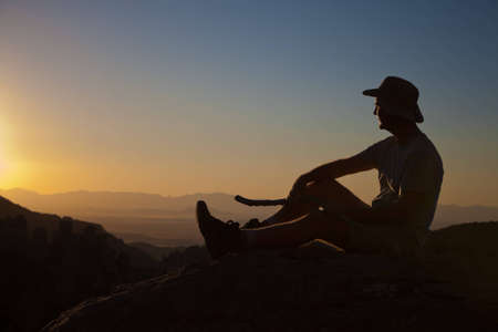 Mature man rest from hikingto enjoy the sunset on top of a mountain