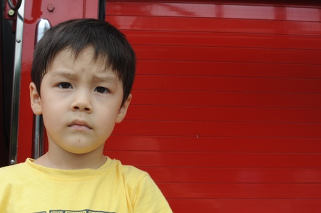 Young boy standing in front of red wall