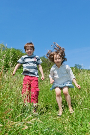two children playing together in the grass