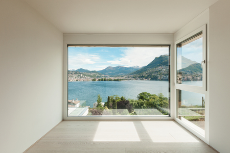 Room with wide window overlooking landscape with lake surrounded ...