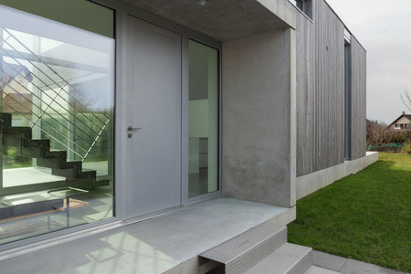 Foto de Entrance of a modern house in concrete and wood, outside - Imagen libre de derechos
