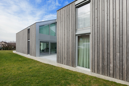 Photo pour Exterior of a modern house in cement and wood, lawn - image libre de droit