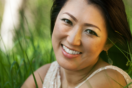 Asian woman sitting in the meadow