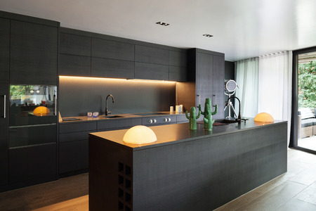 Photo pour Modern kitchen with black furniture and wooden floor - image libre de droit