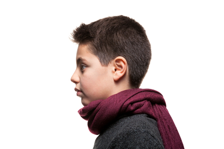 Photo pour Boy wearing woolen sweater and red scarf, portrait in studio, profile view - image libre de droit