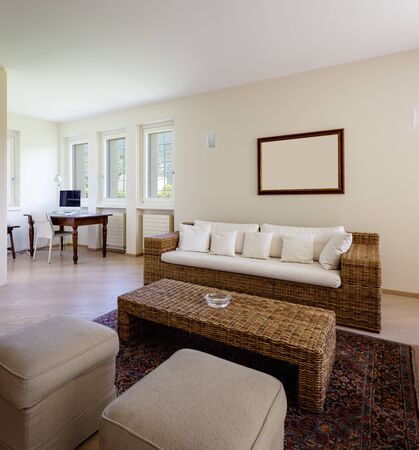Photo pour Modern living room with wicker furniture in a design villa. Nobody inside - image libre de droit