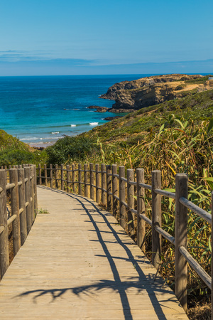 Wooden path on the beach of a natural park in Portugal with ocean view