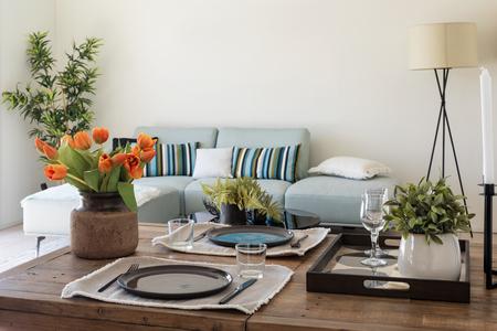 Foto de Wooden table detail with plates, cutlery and bunch of orange tulips. Modern design living room. Nobody inside - Imagen libre de derechos