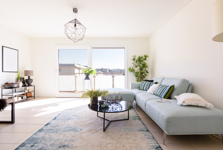 Photo pour Modern living room with designer sofa and coffee table. Window with view. Nobody inside - image libre de droit