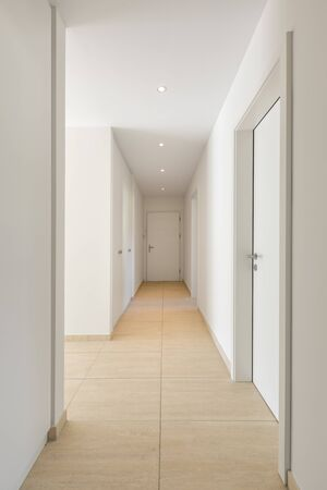 Photo pour Corridor with travertine floor, white walls and built-in wardrobes. Nobody inside - image libre de droit