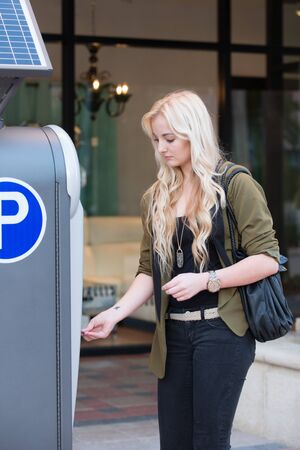 Young woman model paying interfacing with a parking meter