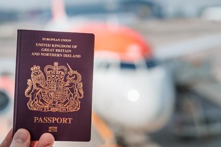 Foto de A red British passport held up against a background of a generic plane on a bright sunny day - Imagen libre de derechos