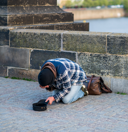 Photo for Cold Homeless man on his knees begging for money from tourists on the Charles Bridge in Prague - Spring 2019 - Royalty Free Image