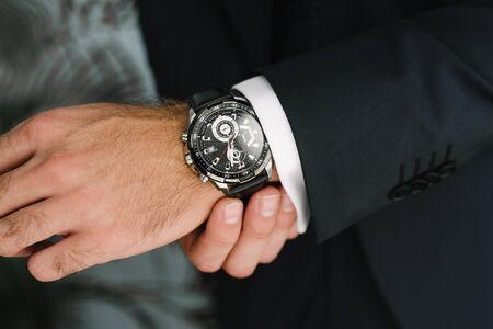 Photo pour A man in a suit adjusts the clock on his hand - image libre de droit