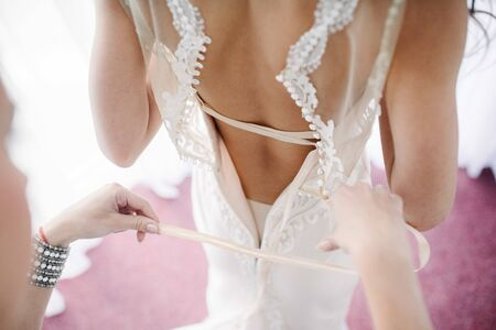 Photo for A white wedding dress is knitted to the bride. A bride is being helped to wear the wedding dress. The bride's preparation for the wedding - Royalty Free Image