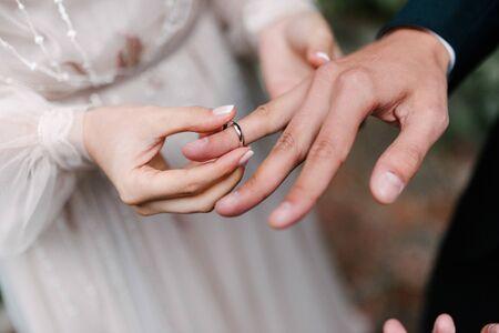 Photo pour The bridegroom puts the wedding ring on the bride close up. - image libre de droit