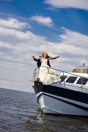 Happy bride and groom on a luxury yacht