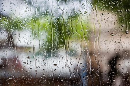 heavy rain drops on window with green background