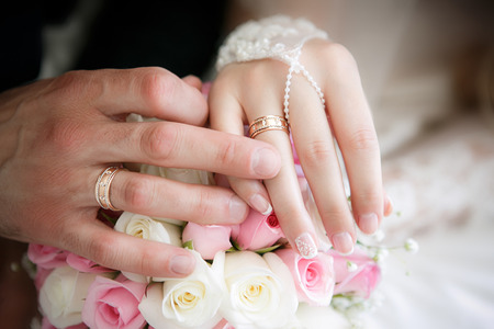 Foto de Hands of the groom and the bride with wedding rings and a wedding bouquet from roses - Imagen libre de derechos