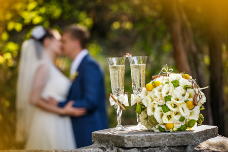 Wedding rings with roses and glasses of champagne and a kiss of the groom and bride on a background