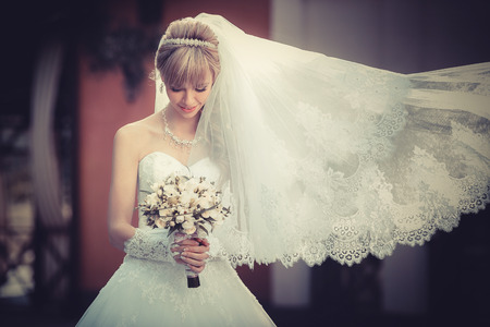 Portrait of a beautiful blonde bride with wedding bouqet in the hands