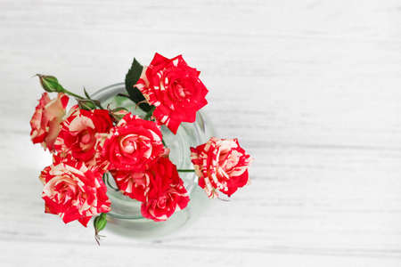 Photo for Bouquet of red roses in a vase on a white background from boards. - Royalty Free Image