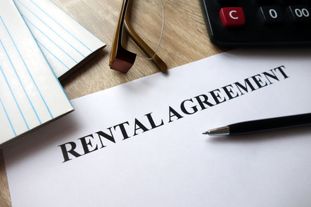 Photo pour Rental agreement form with pen, calculator and glasses on desk - image libre de droit