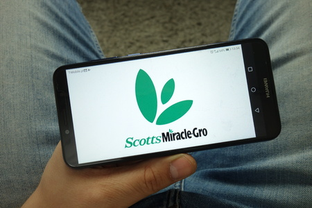 KONSKIE, POLAND - April 13, 2019: Man holding smartphone with the Scotts Miracle-Gro Company logo