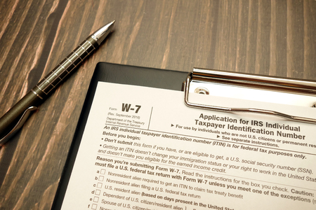 Tax form W-7 for Non-US-citizens for avoid US withholding tax and pen on wooden desk