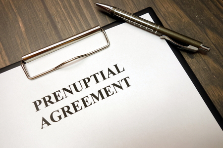 Foto de Clipboard with prenuptial agreement and pen on wooden desk background - Imagen libre de derechos