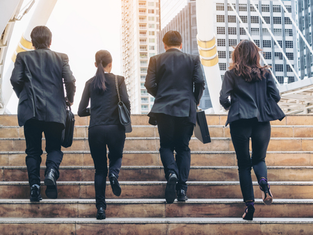 Foto de Lively business team running in the city. Group of businessmen and businesswomen wearing full business suit with business buildings background. Teamwork, togetherness, liveliness, business concept. - Imagen libre de derechos