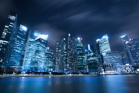 Modern city skyline at night with illuminated skyscrapers over water surface. Singapore central business district city skyline at marina bay. Modern architecture. Skyscrapers in Singapore downtown.
