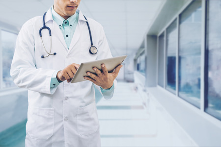 Medical concept - Male doctor working on computer tablet wearing doctors uniform in a hospital or doctors office. Concept of medical data analysis by doctor, medical technology and doctors data.