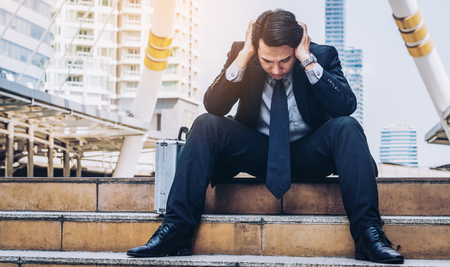 Photo for Desperate businessman sitting hopelessly on stair floor in central business district due to unemployment. Concept of failure, desperation, unemployment and business depression. - Royalty Free Image