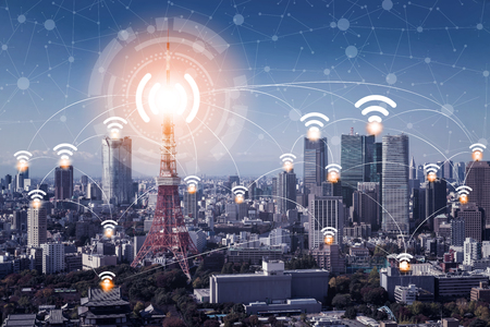 Foto de Smart city wireless communication network with graphic showing concept of internet of things ( IOT ) and information communication technology ( ICT ) against modern city buildings in the background. - Imagen libre de derechos