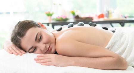 Foto de Woman getting hot stone massage treatment by professional beautician therapist in spa salon. Luxury wellness, back stress relief and rejuvenation concept. - Imagen libre de derechos